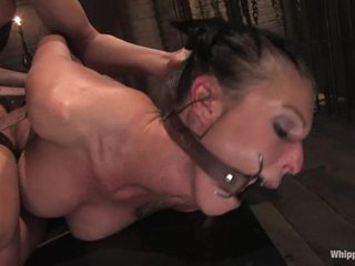 Tied up and gagged slut gets drilled in the a-hole with a dildo by another whore.