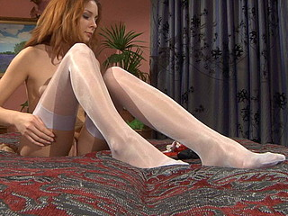 Red-haired mischief adjusting grey high shine nylons with a red garter
