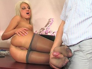 Golden-Haired chick in shiny grey hose is about to service schlong with her feet