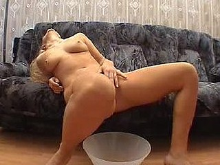 Sexy nude blondie urinates into a vessel