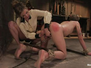 Hell hath no fury like the woman scorned. This is an apt example of it. His butt is already red from the spanking that he has received at the hand of her mistress who has him tethered to a hook. After spanking him she gives him her hot round ass as she wiggles her hot booty just out of his range.