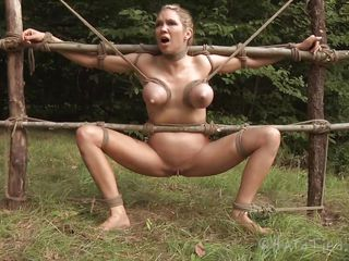 It's clear that the blonde milf Rain is a city girl. Perhaps the fact that she's tied on that wooden structure and mouth fucked brutally in the middle of that green field will make her appreciate the beauty of nature? Well, at least she look great with her big boobs tied and squeezed and that tight pussy filled up.