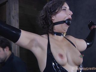 Brunette Marina wearing a black latex suit and having a big black ball gagging her mouth is about to be punished by her executor. The guy starts with her boobs and uses very big suckers to torture them and when Marine's nipples are hard he ties them with rubber bands. Seems she will stay there for a long time